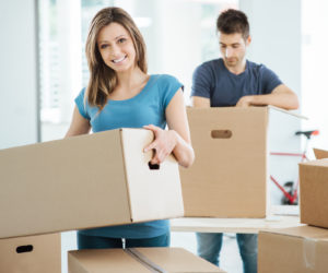 Young happy couple moving in their new house and unpacking boxes, she is carrying a carton box and smiling at camera